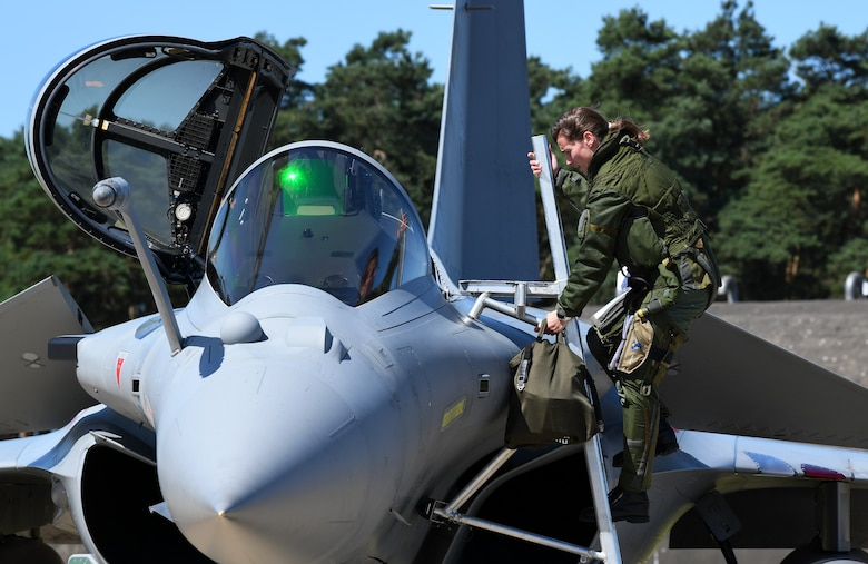 A French Air Force pilot climbs into a Rafale during exercise Point Blank 19-2 at Royal Air Force Lakenheath, England, June 17, 2019. More than 50 aircraft from three nations, U.S., France, and the UK, participated in the exercise promoting interoperability. (U.S. Air Force photo by Staff Sgt. Alex Fox Echols III/Released)
