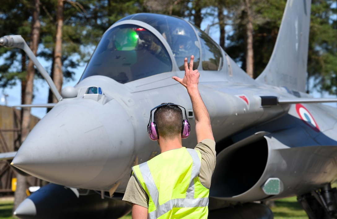 A French Air Force maintainer signals a Rafale pilot during exercise Point Blank 19-2 at Royal Air Force Lakenheath, England, June 17, 2019. During this trilateral exercise, participating air forces are enhancing professional relationships and improving overall coordination with allies and partner militaries during times of crisis. (U.S. Air Force photo by Staff Sgt. Alex Fox Echols III/Released)