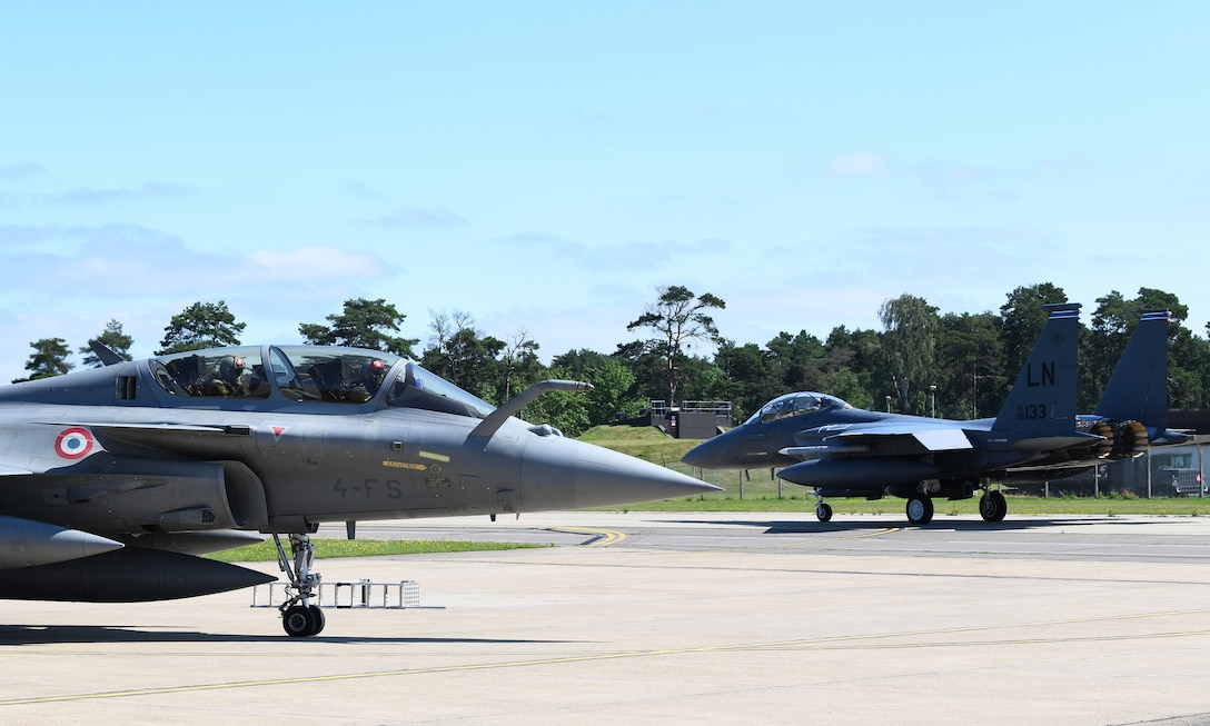 An F-15E Strike Eagle taxis past a French Air Force Rafale during exercise Point Blank 19-2 at Royal Air Force Lakenheath, England, June 17, 2019. More than 50 aircraft from three nations, U.S., France, and the UK, participated in the exercise promoting interoperability. (U.S. Air Force photo by Staff Sgt. Alex Fox Echols III/Released)