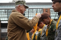 Adm. Craig S. Faller, places a first place ribbon around a Colombian service member.