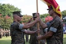 U.S. Marine Corps Col. Thomas H. Campbell III, right, the outgoing commanding officer of Headquarters and Service Battalion, U.S. Marine Corps Forces Command, passes the colors to Col. Mark R. Reid, the incoming battalion commanding officer, during a change of command ceremony at Naval Support Activity Hampton Roads, Virginia, June 27, 2019.