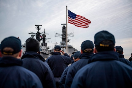 Sailors salute the flag.