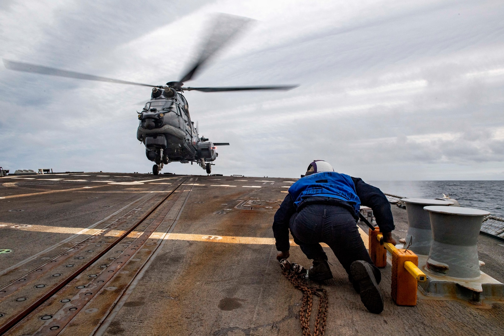 A U.S. Navy sailor prepares to chock and chain a helicopter.
