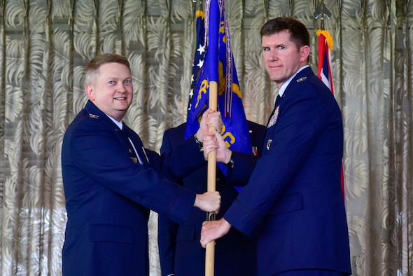 U.S. Air Force Col. Max Pearson, 480th Intelligence, Surveillance and Reconnaissance Wing commander, hands the guidon to Col. Eric Mack, 692nd ISR Group commander, during a change of command ceremony at Joint Base Pearl Harbor-Hickam, Hawaii, June 27, 2019. Mack joins the 692nd ISRG after serving as the Chief of ISR Force Readiness at the Pentagon in Washington, D.C. (U.S. Air Force photo by Senior Airman Douglas Lorance)