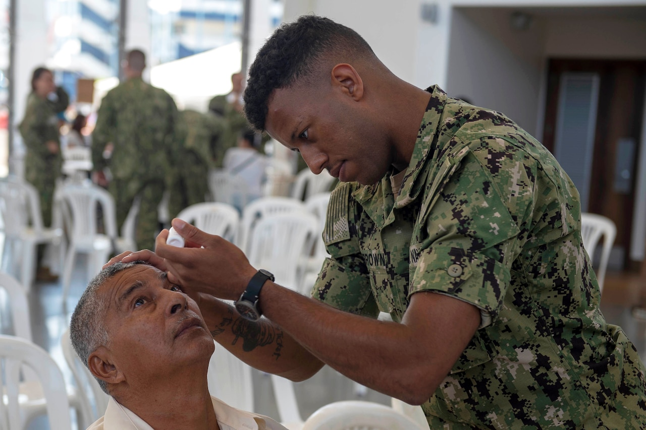 A sailor puts drops into a man's eyes.