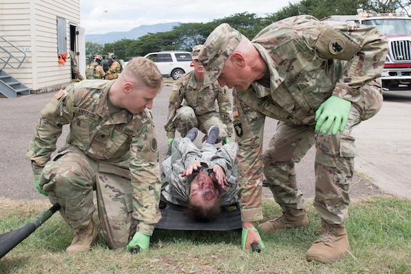 U.S. Army medics from Joint Task Force - Bravo Medical Element transport a burn victim to a casualty collection point during a joint training exercise, June 26, 2019, at Soto Cano Air Base, Honduras. Members from Joint Task Force – Bravo's Medical Element, 612th Air Base Squadron firefighters and 480th Military Police Company worked together to accomplish goals during the training event. The event involved the firefighters entering a smoke-filled building to recover burn casualties while the Medical Element performed triage at the scene. The 480TH MPC members provided a cordon of the area and kept rioting personnel from entering the scene. (U.S. Air Force photo by Staff Sgt. Eric Summers Jr.)
