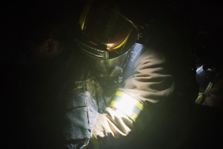 A U.S. Air Force firefighter from the 612th Air Base Squadron carries a simulated burn victim from a smoke-filled building during a joint training exercise, June 26, 2019, at Soto Cano Air Base, Honduras. Members from Joint Task Force – Bravo's Medical Element, 612th Air Base Squadron firefighters and 480th Military Police Company worked together to accomplish goals during the training event. The event involved the firefighters entering a smoke-filled building to recover burn casualties while the Medical Element performed triage at the scene. The 480TH MPC members provided a cordon of the area and kept rioting personnel from entering the scene. (U.S. Air Force photo by Staff Sgt. Eric Summers Jr.)