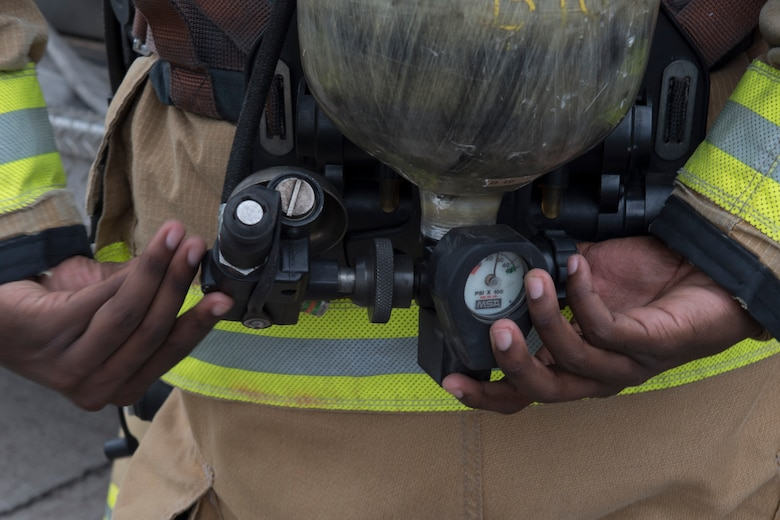 A U.S. Air Force firefighter from the 612th Air Base Squadron adjusts valves on his oxygen tank before entering a smoke-filled building during a joint training exercise June 26, 2019, at Soto Cano Air Base, Honduras. Members from Joint Task Force – Bravo's Medical Element, 612th Air Base Squadron firefighters and 480th Military Police Company worked together to accomplish goals during the training event. The event involved the firefighters entering a smoke-filled building to recover burn casualties while the Medical Element performed triage at the scene. The 480TH MPC members provided a cordon of the area and kept rioting personnel from entering the scene. (U.S. Air Force photo by Staff Sgt. Eric Summers Jr.)