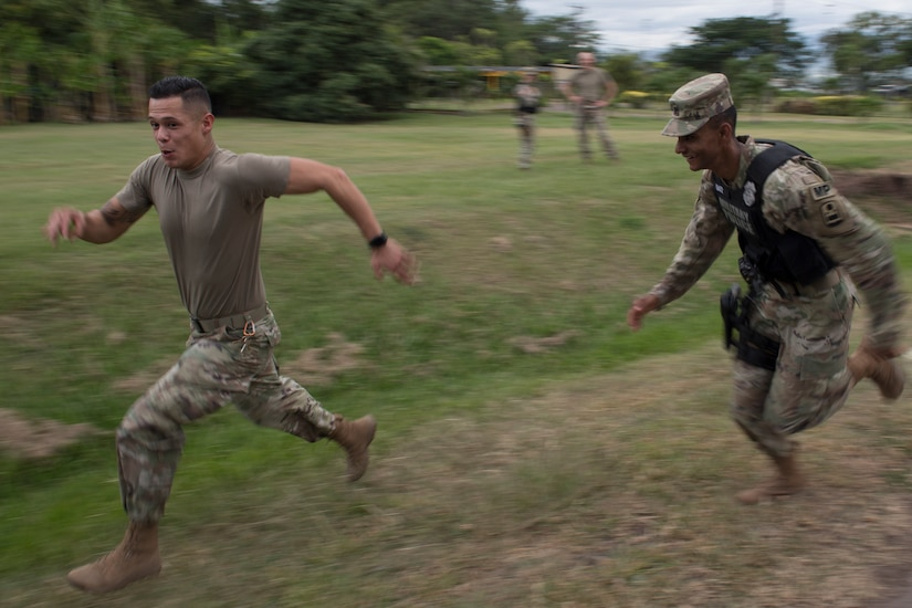 U.S. Army Spc. William Baez-Santos (left), 480th Military Police Company Forward 1 patrolman, chases down a simulated rioter during a joint training exercise June 26, 2019, at Soto Cano Air Base, Honduras. Members from Joint Task Force – Bravo's Medical Element, 612th Air Base Squadron firefighters and 480th Military Police Company worked together to accomplish goals during the training event. The event involved the firefighters entering a smoke-filled building to recover burn casualties while the Medical Element performed triage at the scene. The 480TH MPC members provided a cordon of the area and kept rioting personnel from entering the scene. (U.S. Air Force photo by Staff Sgt. Eric Summers Jr.)