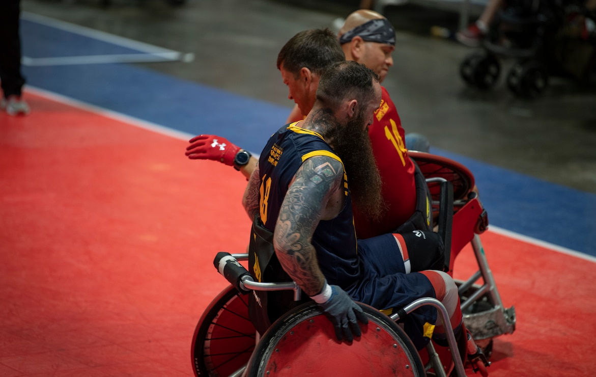 U.S. Navy team members make a Marine Corps sandwich with Staff Sgt. Jason Pritchett during the DoD Warrior Games Wheelchair Rugby competition in Tampa, Florida, June 27, 2019. The DoD Warrior Games is an adaptive sports competition for wounded, ill and injured service members and veterans. The 2019 Warrior Games consist of 13 Paralympic-style sports, and more than 300 athletes representing the U.S. Marine Corps, Army, Navy, Air Force, Special Operations Command, and five international teams.