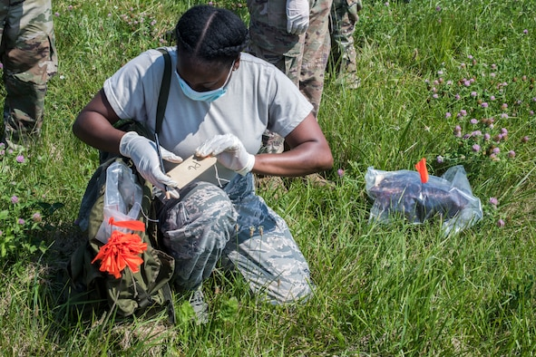 Senior Airman Taiyon Perkins, 436th Force Support Squadron fitness support supervisor, marks a newfound item during a search-and-recovery exercise June 28, 2019, at Dover Air Force Base, Del. Perkins labeled each item with a letter and a number to indicate the type of item that was located for logging purposes. (U.S. Air Force photo by Senior Airman Christopher Quail)