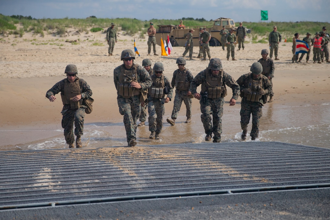 U.S Marines with 2nd Transportation Support Battalion, Combat Logistics Regiment 2, 2nd Marine Logistics Group, run aboard a Navy improved navy lighterage system during exercise Resolute Sun at Fort Story, Virginia, June 17, 2019. Marines participated in the exercise to increase combat operational readiness in amphibious and prepositioning operations while conducting joint training with U.S. Army during a joint logistics over the shore scenario.