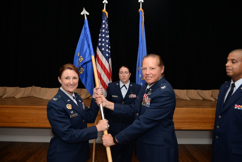U.S. Air Force Col. Beatrice Dolihite, 81st Medical Group commander, takes the guidon from Col. Stephanie Buffett, outgoing 81st Diagnostics and Therapeutics Squadron commander, during a change of command ceremony inside the Don Wylie Auditorium on Keesler Air Force Base, Mississippi, June 27, 2019. The passing of the guidon is a ceremonial symbol of exchanging command from one commander to another. (U.S. Air Force photo by Airman 1st Class Spencer Tobler)