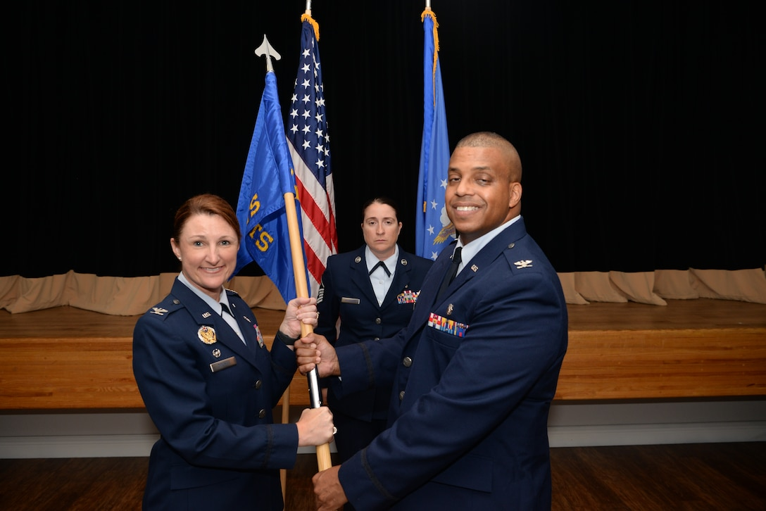 U.S. Air Force Col. Beatrice Dolihite, 81st Medical Group commander, passes the guidon to Col. Trent Tate, incoming 81st Diagnostics and Therapeutics Squadron commander, during a change of command ceremony inside the Don Wylie Auditorium on Keesler Air Force Base, Mississippi, June 27, 2019. The passing of the guidon is a ceremonial symbol of exchanging command from one commander to another. (U.S. Air Force photo by Airman 1st Class Spencer Tobler)