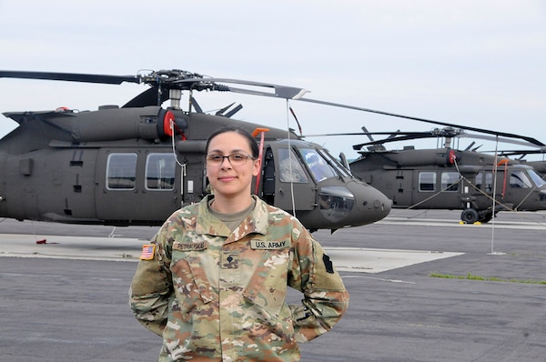 U.S. Army Spc. Courtney Petrauskas, information technology specialist with Headquarters and Headquarters Company, 28th Expeditionary Combat Aviation Brigade, poses for a photo in front of UH-60 Black Hawk helicopters at Muir Army Airfield.