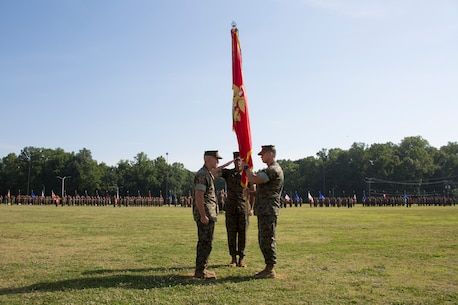 U.S. Marine Corps Col. Brian W. Neil, right, the outgoing commanding officer of Marine Corps Security Force Regiment, U.S. Marine Corps Forces Command, passes the colors to Col. Corey M. Collier, the incoming regiment commanding officer, during a change of command ceremony at Naval Weapons Station Yorktown, Yorktown, Virginia, June 28, 2019. The change of command is a time-honored tradition where the responsibilities and authority of command are ceremoniously passed from one commander to the next. (U.S. Marine Corps photo by Sgt. Jessika Braden/ Released)