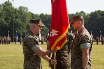 U.S. Marine Corps Col. Corey M. Collier, left, the incoming commanding officer of Marine Corps Security Force Regiment, U.S. Marine Corps Forces Command, takes the regiments colors from Col. Brain W. Neil, the outgoing regiment commanding officer, during a change of command ceremony at Naval Weapons Station Yorktown, Yorktown, Virginia, June 28, 2019. The change of command is a time-honored tradition where the responsibilities and authority of command are ceremoniously passed from one commander to the next. (U.S. Marine Corps photo by Sgt. Jessika Braden/ Released)