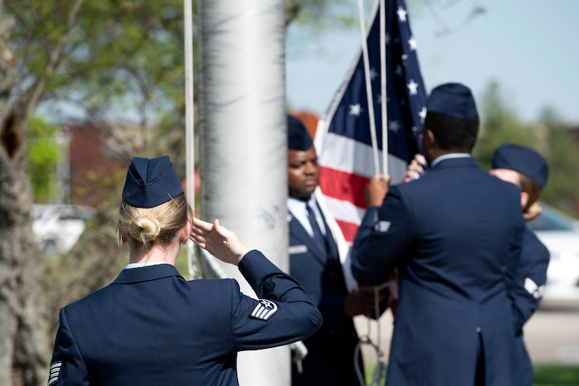 Airman saluting flag.