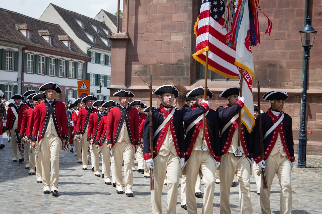 Army music unit wearing 18th-century style uniforms participates in parade.