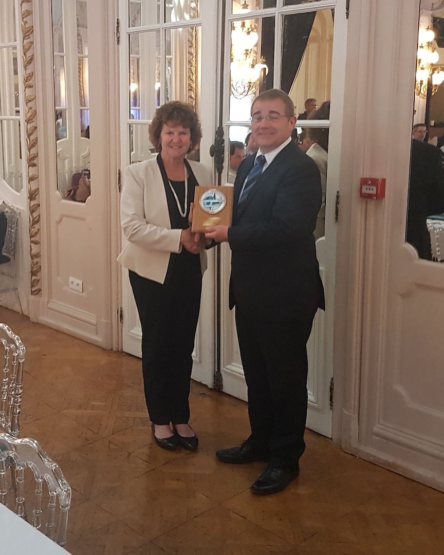 Elaine Chapman, Defense Logistics Agency Logistics Operations employee and new chair of Allied Committee 135's Main Group, presents a plaque to the previous chair, Thierry Vanden Dries of Belgium after he turned over the chair to her in Reims, France, at the Main Group.