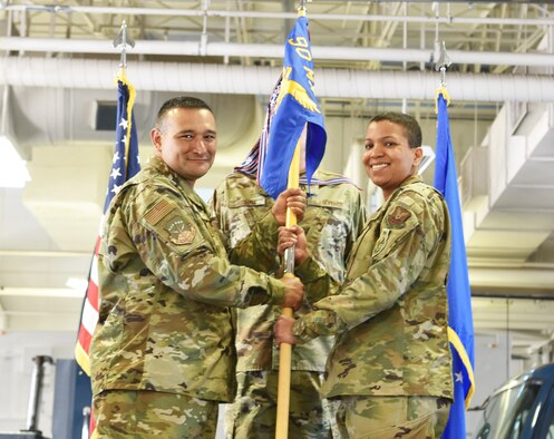 Colonel Brian Rico, 90th Maintenance Group commander, passes the guidon to Maj. Christine Hernandez, 90th Missile Maintenance Squadron incoming commander, during the 90th MMXS change of command ceremony June 28, 2019, on F.E. Warren Air Force Base, Wyo. The ceremony signified the transition of command from Lt. Col. Stephanie Wilson to Hernandez. (U.S. Air Force photo by 2nd Lt. Emily Seaton)