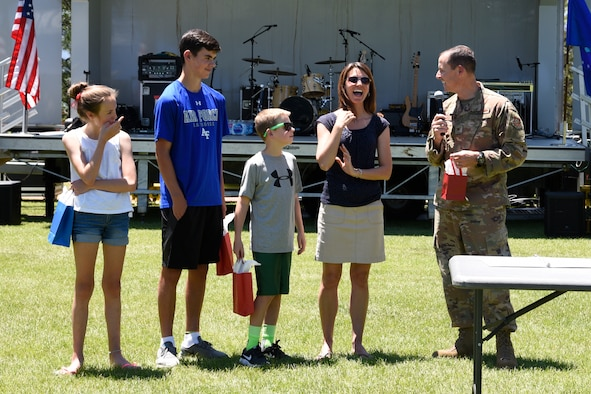 PETERSON AIR FORCE BASE, Colo. – Col. Todd Moore, 21st Space Wing commander, hands out gifts to his wife and three children at his going-away ceremony, June 28, 2019 at Peterson Air Force Base, Colorado. Moore thanked his family for being supportive during his time here at the wing. Moore and his family will be staying in Colorado Springs for his next assignment with the Space Security & Defense Program. (U.S. Air Force photo by Staff Sgt. Alexandra M. Longfellow)