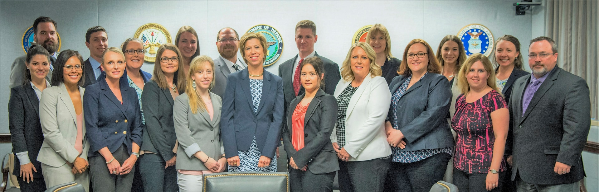 Twenty people in business attire pose for a photo.