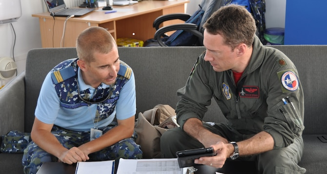 Romanian Air Force Capt. Adrian Tanase, chief of support and movement control compartment, 71st Air Base, Campia Turzii, Romania, and U.S. Air Force Maj. Bryan Spence, a pilot assigned to the 457th Expeditionary Fighter Squadron, 301st Fighter Wing, Joint Reserve Base Fort Worth, Texas, discuss a training flight in the tower at the 71st Air Base, Campia Turzii, Romania, June 27, 2019. While in theater, these personnel and aircraft will participate in multiple readiness exercises alongside NATO allies and partners to strengthen interoperability and to demonstrate U.S. commitment to the security and stability of Europe. Portions of this image were masked for security reasons. (U.S. Air Force photo by Master Sgt. Megan Crusher)