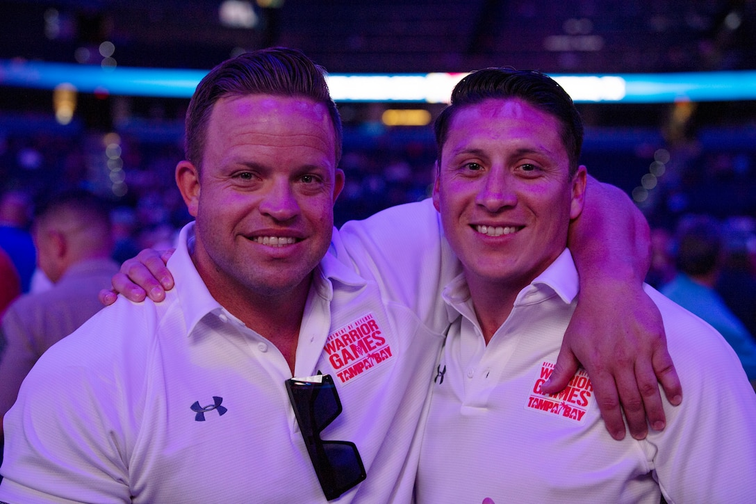 U.S. Marine Corps Gunnery  Sgt. Steven McKay and Staff Sgt. Jason Pacheco celebrate at the 2019 Warrior Games closing ceremony at Amalie Arena in Tampa, Florida, June 30. The DoD Warrior Games is an adaptive sports competition for wounded, ill and injured service members and veterans. The 2019 Warrior Games consist of 13 Paralympic-style sports, and more than 300 athletes representing the U.S. Marine Corps, Army, Navy, Air Force, Special Operations Command, and five international teams.