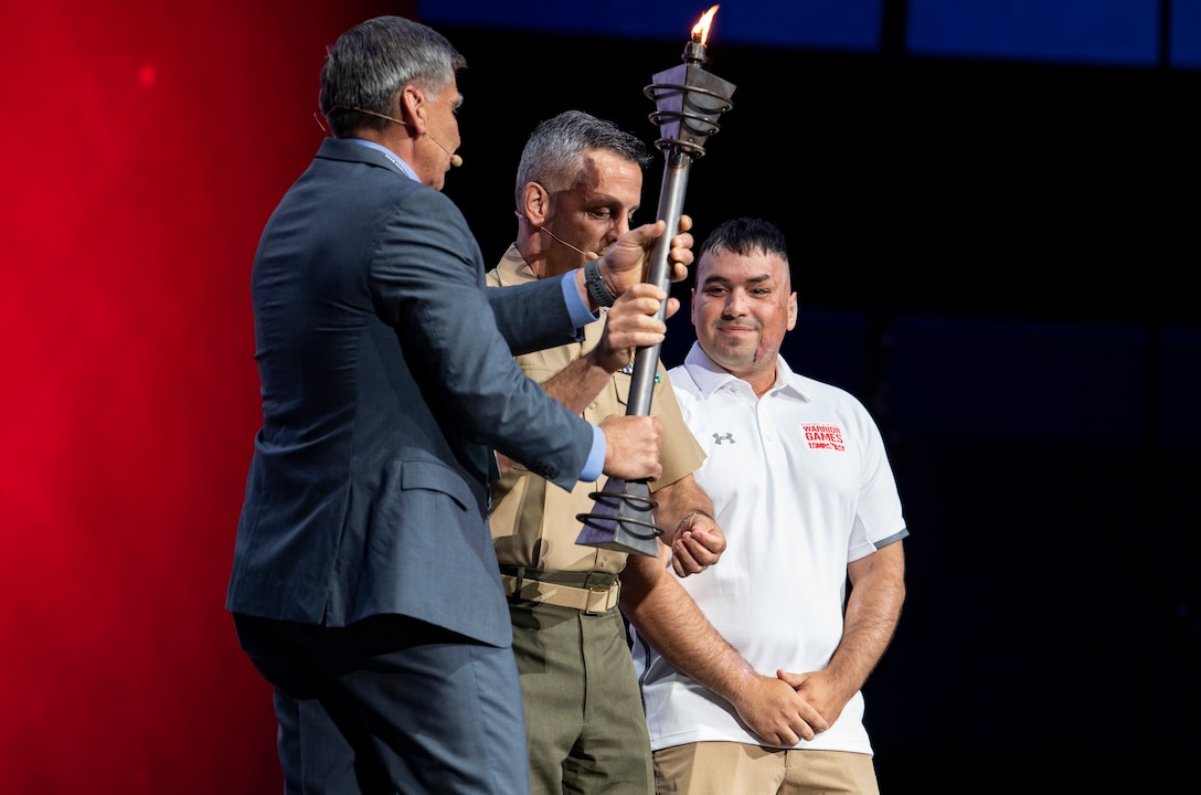 Lt. Gen Michale Rocco, Deputy Commandant for Manpower and Reserve Affairs, and Maj. Gen. Juan Ayala (Ret.), City of San Antonio Director of Military Affairs, receive the torch to signify the transition of DoD Warrior Games host service at Amalie Arena, Tampa, Florida, June 30, 2019. Next year's games will be hosted by the U.S. Marine Corps in San Antonio, Texas. The 2019 Warrior Games consist of 13 Paralympic-style sports, and more than 300 athletes representing the U.S. Marine Corps, Army, Navy, Air Force, Special Operations Command, and five international teams.