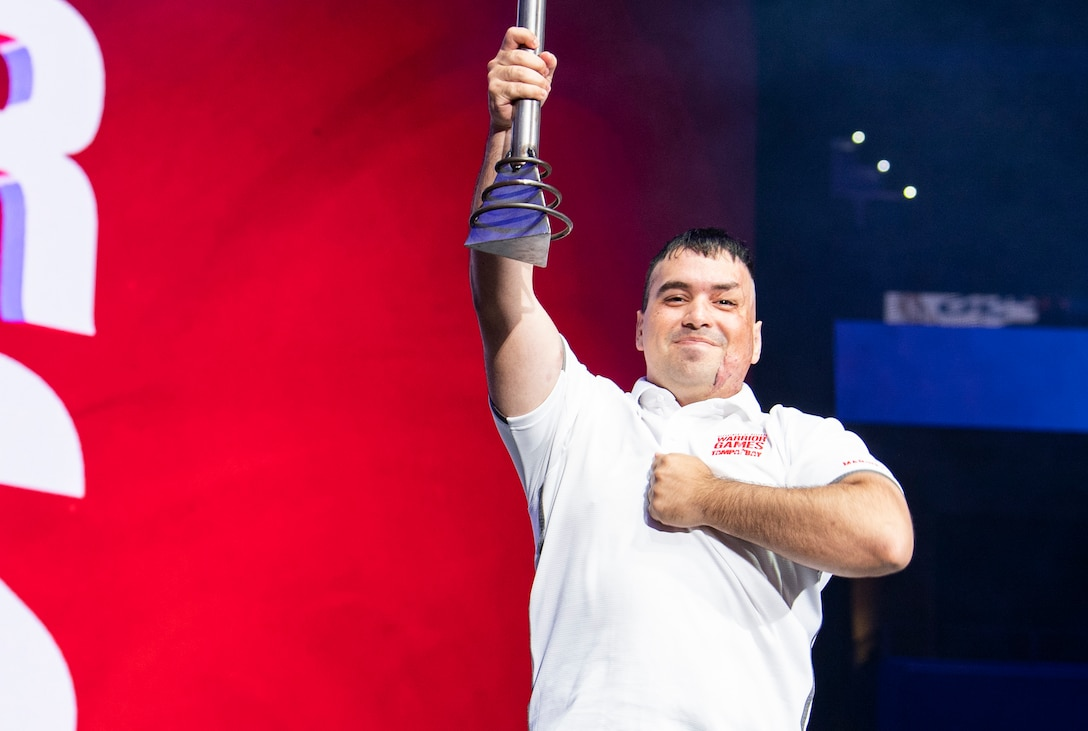 U.S. Marine Corps Cpl. Matthew Maddux holds the DoD Warrior Games ceremonial torch high during the closing ceremony at Amalie Arena, in Tampa, Florida, June 30, 2019. Maddux is the ambassador for next year's games, which will be hosted by the U.S. Marine Corps in San Antonio, Texas. The Warrior Games showcase the resilient spirit of today's wounded, ill or injured service members from all branches of the military and provide a venue for recovering service members and veterans to demonstrate triumph over significant physical or invisible wounds and injuries.