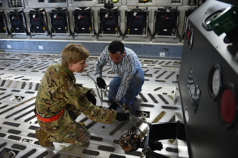 Gen. Maryanne Miller, Air Mobility Command commander, tightens chains on a piece of cargo inside a C-17 Globemaster III alongside Robert Izzeff, 62nd Aerial Port Squadron aerial port expediter load director, June 25, 2019, at Joint Base Lewis-McChord, Wash.