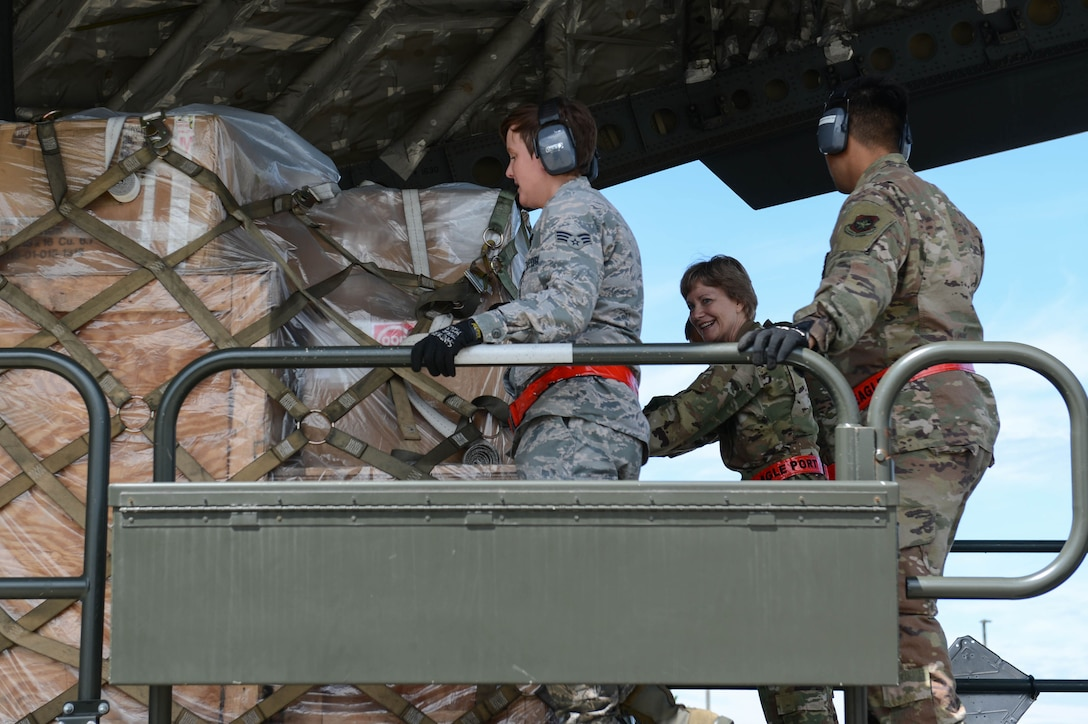 Gen. Maryanne Miller, Air Mobility Command commander, center, and 62nd Aerial Port Squadron Airmen push a pallet of cargo onto a C-17 Globemaster III, June 25, 2019, at Joint Base Lewis-McChord, Wash.
