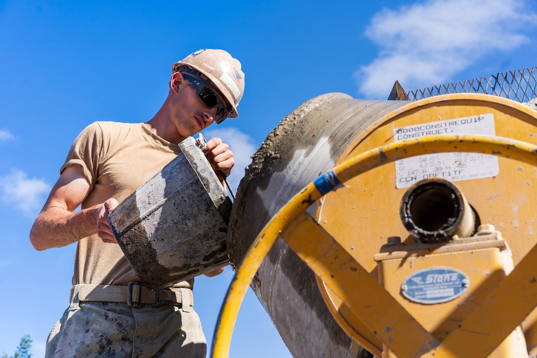 A sailor is seen from a low angle pouring material into a construction machine.