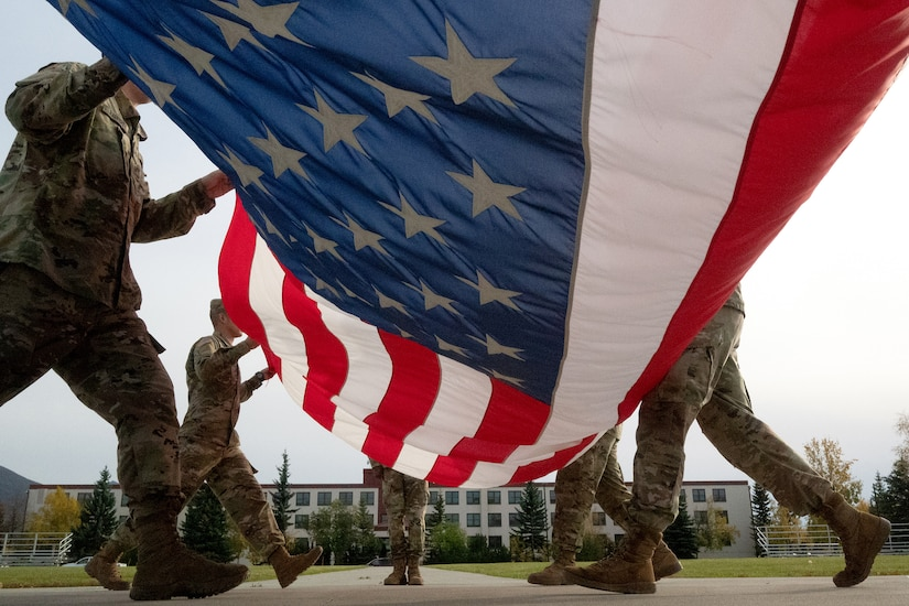 Soldiers fold a flag.