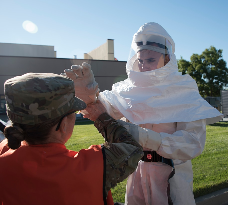 U.S. Air Force Capt. Shannon Hewitt, 60th Medical Operations Squadron, left, assists with a powered air-purifying respirator training suit June 27, 2019, at Travis Air Force Base, California. The suit was part of a hazardous material exercise at David Grant USAF Medical Center. (U.S. Air Force photo by Staff Sgt. Amber Carter)