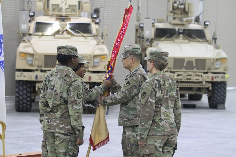 Colonel Ralph T. Borja, center, outgoing commander, 408th Contracting Support Brigade, accepts the unit colors from Command Sgt. Maj. DuJuania Deloatch, senior enlisted leader, 408th CSB, during a change of command ceremony at Camp Arifjan, Kuwait, June 27, 2019. Borja led the 408th CSB since June 2018 and ensured the successful awarding, management and support for more than $11 billion in contracts across the U.S. Army Central area of operations.