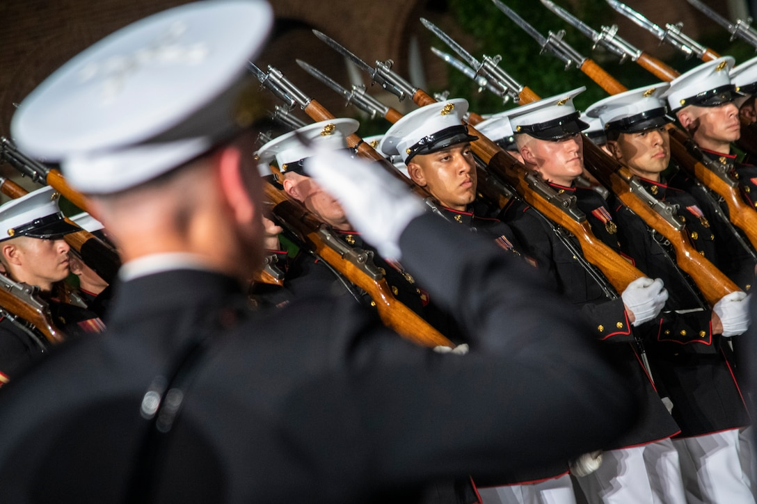 A group of Marines stand at attention while being saluted.