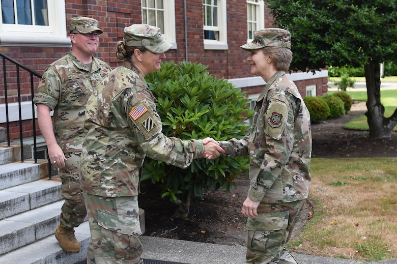 U.S. Army Colonel Nicole Lucas, Joint Base garrison commander, middle, and Col. Bill Percival, 627th Air Base Group and Joint Base deputy commander, far left, greet Gen. Maryanne Miller, Air Mobility Command commander, June 26, 2019 in front of Joint Base Headquarters at Joint Base Lewis-McChord, Wash.