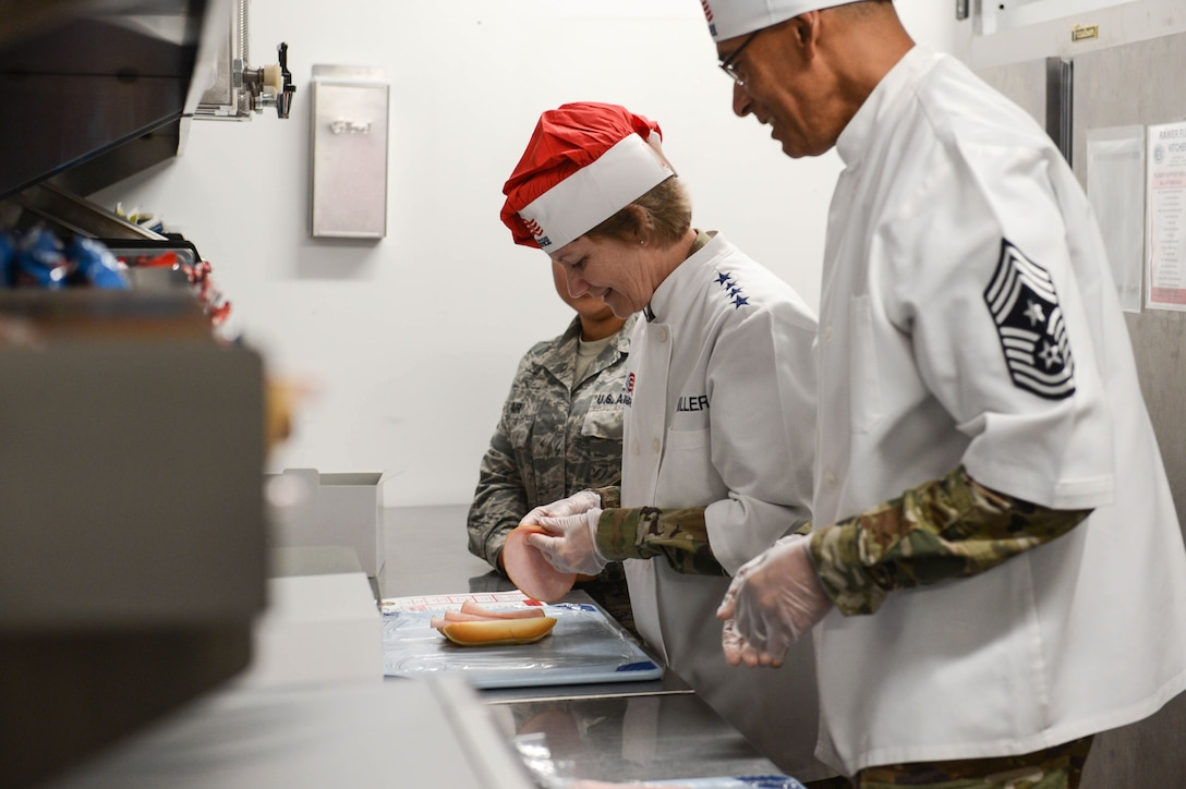 Gen. Maryanne Miller, Air Mobility Command commander, and Chief Master Sgt. Terrence Greene, AMC command chief, make boxed meals at the 627th Force Support Squadron flight kitchen June 26, 2019, at Joint Base Lewis-McChord, Wash.