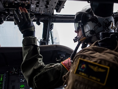 A pilot conducts pre-flight checks on a helicopter.