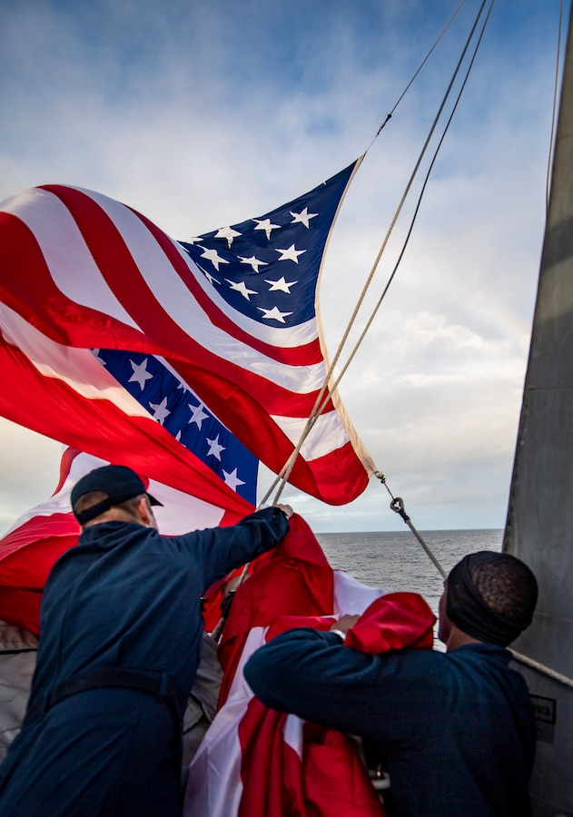 Sailors close up the battle ensign aboard USS Michael Murphy.