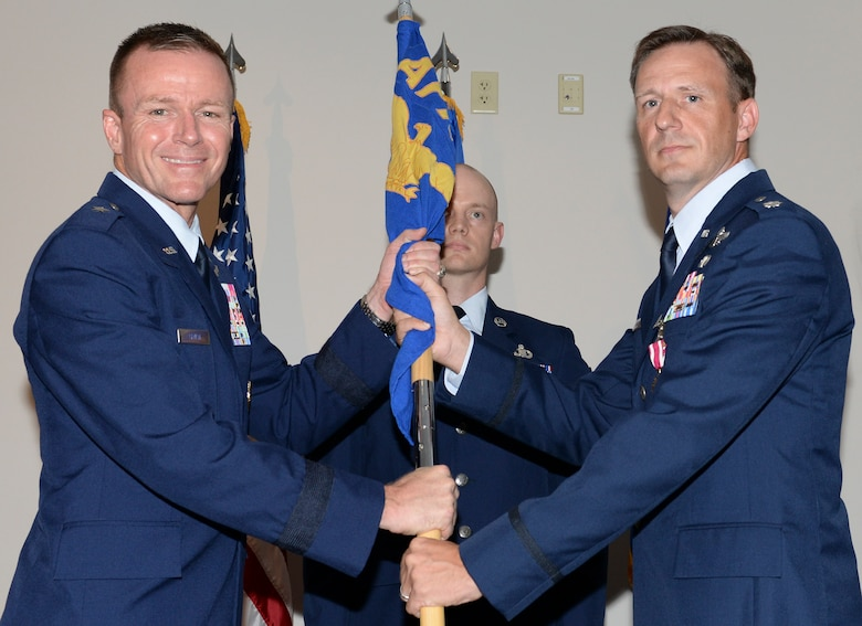 U.S. Air Force Lt. Col. Evan H. Gardner, outgoing commander, Air Force Rescue Coordination Center relinquishes the AFRCC guidon to Brig. Gen. Kenneth P. Ekman, vice commander, 1 AF (Air Forces Northern), during a change of command ceremony July 2, 2019, Tyndall AFB, Fla.