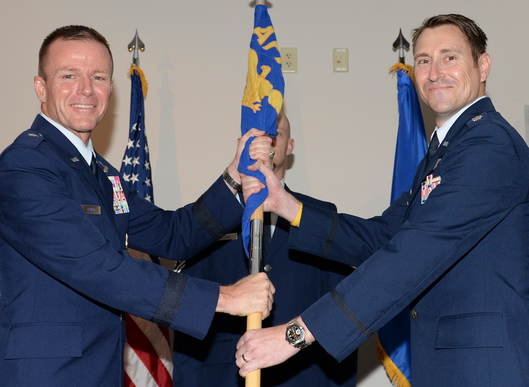 U.S. Air Force Lt. Col. Gene M. Manner, commander, Air Force Rescue Coordination Center accepts the AFRCC guidon from Brig. Gen. Kenneth P. Ekman, vice commander, 1 AF (Air Forces Northern), during a change of command ceremony July 2, 2019, Tyndall AFB, Fla.