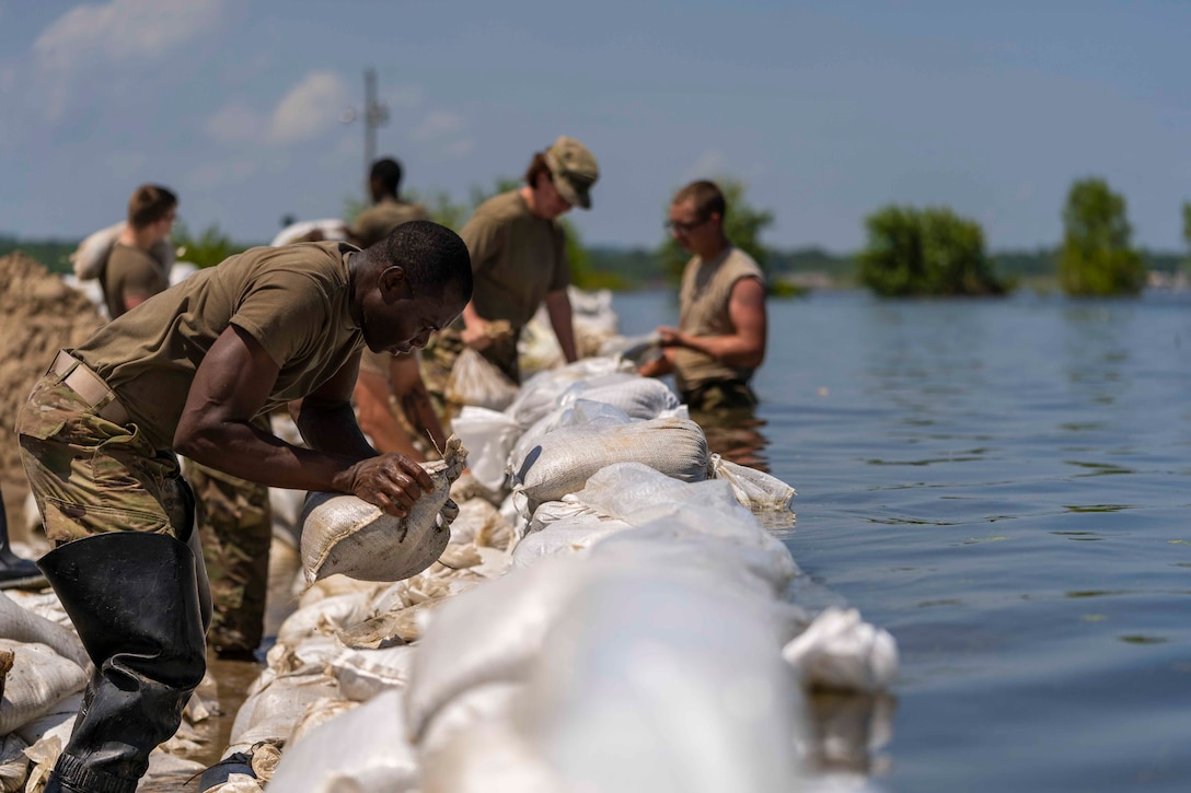 Soldiers lay sandbags at a flooded area.