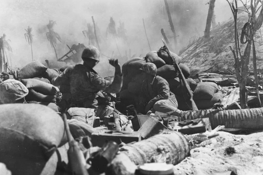 Marines hide behind sandbags during heavy combat beside a hill; one Marine's hand is cocked backward, ready to launch a grenade into the distance. Sand is in the foreground; palm trees are in the background.