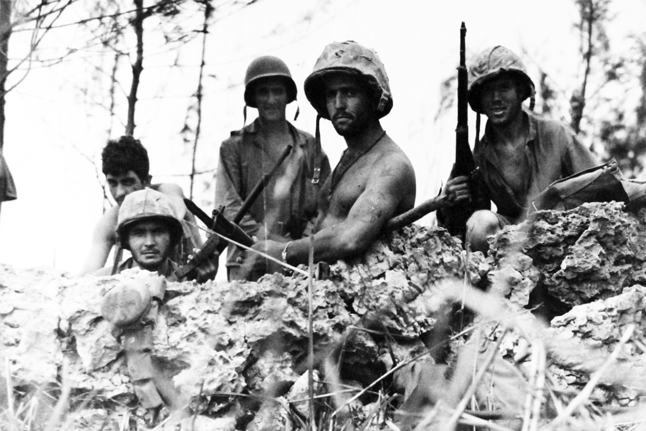 Five Marines wearing combat helmets and holding guns stand in a foxhole with sparse trees in the background.