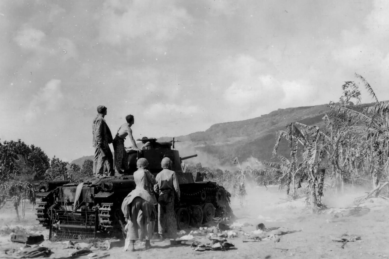 Four service members, two of whom are standing on a tank, look into the distance toward an island hill. Palm trees and sand surround them.