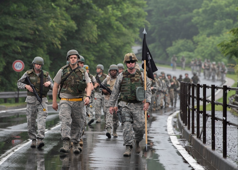 """Airmen with the 35th Logistics Readiness Squadron ruck in the rain during an agile combat employment exercise at Misawa Air Base, Japan, June 28, 2019. The members performed a loose formation ruck to """"Camp Defender,"""" where they learned how to move, shoot and communicate during realistic training scenarios. (U.S. Air Force photo by Staff Sgt. Brittany A. Chase)"""