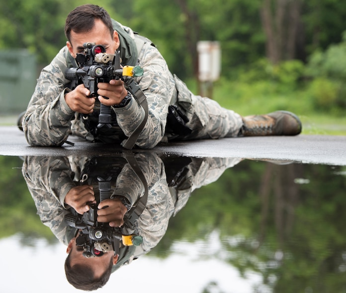 """U.S. Air Force Senior Airman Dylan White, a 35th Security Forces Squadron military working dog handler, lays in the """"prone"""" position during an agile combat employment exercise at Misawa Air Base, Japan, June 28, 2019. White taught 35th Logistic Readiness Squadron how to move, shoot and communicate and applied their newly learned skills to realistic training scenarios, such as clearing buildings and shooting techniques during ACE. (U.S. Air Force photo by Staff Sgt. Brittany A. Chase)"""